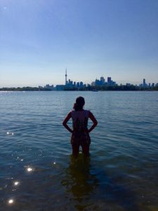 Maya looking at Toronto while standing in Lake Ontario